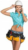 picture of hard-on  - Woman in hard hat and tool belt calling on mobile phone - JPG