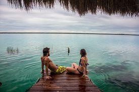 picture of dock a lake  - Bacalar Lake at Riviera Maya Quinatana Roo. Couple sitting on a dock contemplating. Water motion. ** Note: Visible grain at 100%, best at smaller sizes - JPG