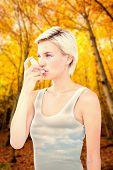 stock photo of inhalant  - Blonde woman taking her inhaler against sky - JPG