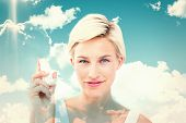 stock photo of inhalant  - Pretty woman holding inhaler smiling at camera against blue sky - JPG