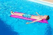 stock photo of mattress  - Caucasian teenage boy lying lazy on his back on air mattress in blue swimming pool - JPG