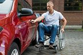 stock photo of handicapped  - Portrait Of A Handicapped Man Sitting On Wheelchair Opening Door Of A Car - JPG