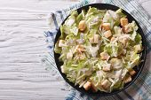 stock photo of caesar salad  - Traditional Caesar salad with croutons and parmesan on a plate - JPG
