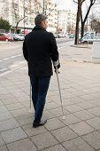 foto of crutch  - Rear View Of A Man Walking On Street Using Crutches - JPG