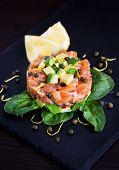 foto of tartar  - Tasty salmon and avocado tartar dark background - JPG