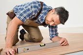 picture of laminate  - Carpenter Installing New Laminated Wooden Floor At Home - JPG