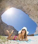 foto of shipwreck  - Woman relaxing on the famous Shipwreck Navagio beach in Zakynthos Greece - JPG