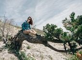 image of juniper-tree  - Beautiful young woman sitting on fairy old tree in summer - JPG