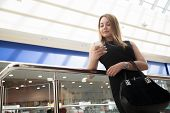 foto of dress-making  - Attractive young woman holding suede handbag wearing black dress making call using app on cell phone texting in shopping center - JPG