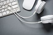 stock photo of mouse  - High Angle View of Modern White Audio Headphones with Cord Mac Computer Keyboard and Mouse on Grey Desk Background with Copy Space - JPG