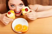 picture of sneak  - Delighted woman hiding behind table sneaking and eating delicious cake with sweet cream and fruits on top - JPG