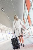image of carry-on luggage  - Full length rear view of young businesswoman with luggage walking in railroad station - JPG