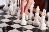 pic of chessboard  - Hand with white pawn on chessboard closeup - JPG