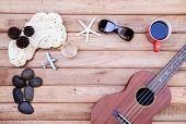stock photo of ukulele  - Cup of coffee and ukulele on wooden background Travel concept - JPG