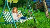 stock photo of ten years old  - Ten years girl playing with tactile tablet sitting on the garden swing - JPG
