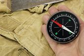 stock photo of tarp  - Male Hand With Magnetic Compass And Machete On The Faded Green Backpack Background Close-up ** Note: Shallow depth of field - JPG