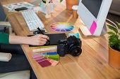 stock photo of color wheel  - Designer working with colour wheel and digitizer in the office - JPG