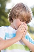 stock photo of blowing nose  - Little boy blowing his nose on a sunny day - JPG