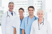 pic of medical office  - Portrait of confident doctors in row at medical office - JPG