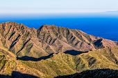 image of horizon  - Coast of Atlantic ocean with green mountain or rock and blue sky with skyline or horizon in Tenerife Canary island Spain at spring or summer
