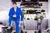 stock photo of auto repair shop  - Mechanic with tire and wheel wrenches gesturing thumbs up against auto repair shop - JPG
