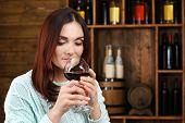 pic of wine cellar  - Young woman tasting wine in cellar - JPG
