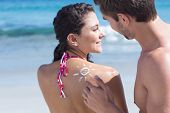 picture of sun-tanned  - Handsome man putting sun tan lotion on his girlfriend at the beach - JPG