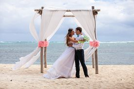 picture of wedding  - young loving couple on their wedding day beautiful wedding arch on beach outdoor beach wedding in tropics  - JPG
