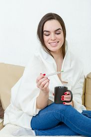 stock photo of feeling better  - Happy woman with thermometer healed of colds flu fever and migraine in bed with cup of tea or coffee - JPG