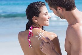 image of sun tan lotion  - Handsome man putting sun tan lotion on his girlfriend at the beach - JPG