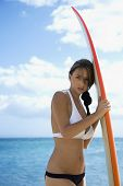 Pretty young Caucasian woman in bikini leaning on surfboard at beach in Maui Hawaii.