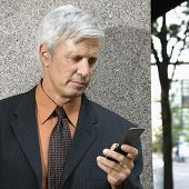 Caucasian middle aged businessman looking down at cell phone.