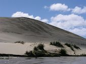 stock photo of quicksand  - sand sledding on te paki quicksand stream - JPG