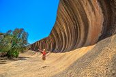 Australian Outback In Hyden Wildlife Park. Carefree Caucasian Woman Jumping At Wave Rock In Hyden, W poster