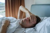 Постер, плакат: Caucasian Man Lying In Bed At Home Suffering From Headache Or Hangover Concept Of Problem With Heal