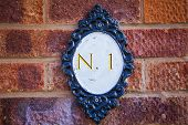 Number One Plate On Brick Wall, English Village, Number One. poster