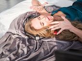 Happy Girl Listening Music Using Headphones And Singing On Bed At Home. People, Leisure And Technolo poster