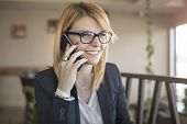 Good Business Talk. Cheerful Young Beautiful Woman In Glasses Talking On Mobile Phone With Smile Whi poster