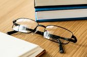 A pair of glasses and books educational, academic and literary concept poster