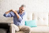 Middle Aged Man Sitting On The Sofa And Holding Painful Shoulder With Another Hand. poster