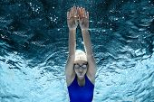Underwater Picture Of Female Swimmer In Swimming Suit And Goggles Training In Swimming Pool poster