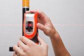 foto of laser beam  - Man hands measuring with laser level gage - JPG
