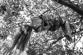 A Young Long Haired Girl Is Hanging From A Tree Tied Up With Ropes In Shibari Fetish Practice - Blac poster