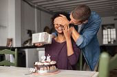 Man giving present to his beloved girlfriend on birthday with cake on table. Cheerful african woman  poster