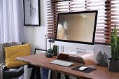 Comfortable Workplace Near Window With Horizontal Blinds In Room poster