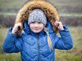 Portrait Of A Child In A Winter Jacket In Summer. The Concept Of Changing The Weather, Climate, Cold poster