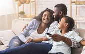 Cheerful Black Family Having Fun Together Watching Tv Show And Switching Channels With Remote Contro poster