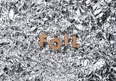 The Word Foil From Wooden Letters On A Background Of Crumpled Foil poster