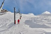 Using ski lift to get to the top of ski slopes poster