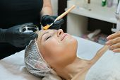 Close-up Face Of Mature Woman At Cosmetic Age Procedures In Beauty Salon, Hands Of Beautician With B poster
